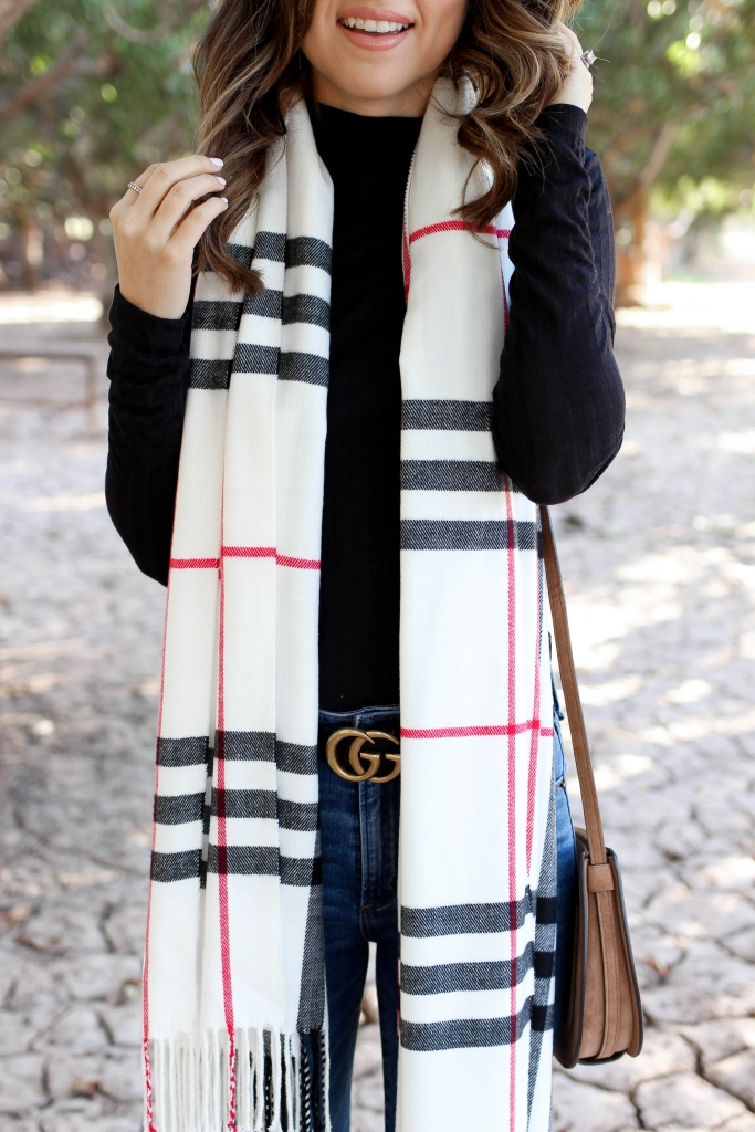a casual black turtleneck outfit with high waisted jeans a plaid scarf and boots