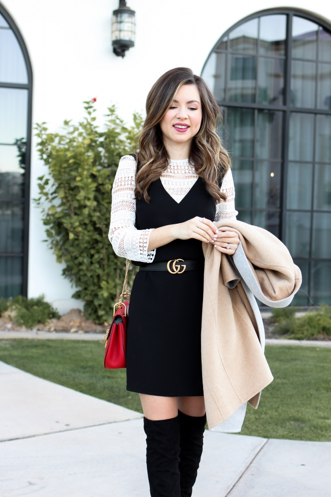 blogger wears a lace shift dress with over the knee boots a peacoat and gucci belt